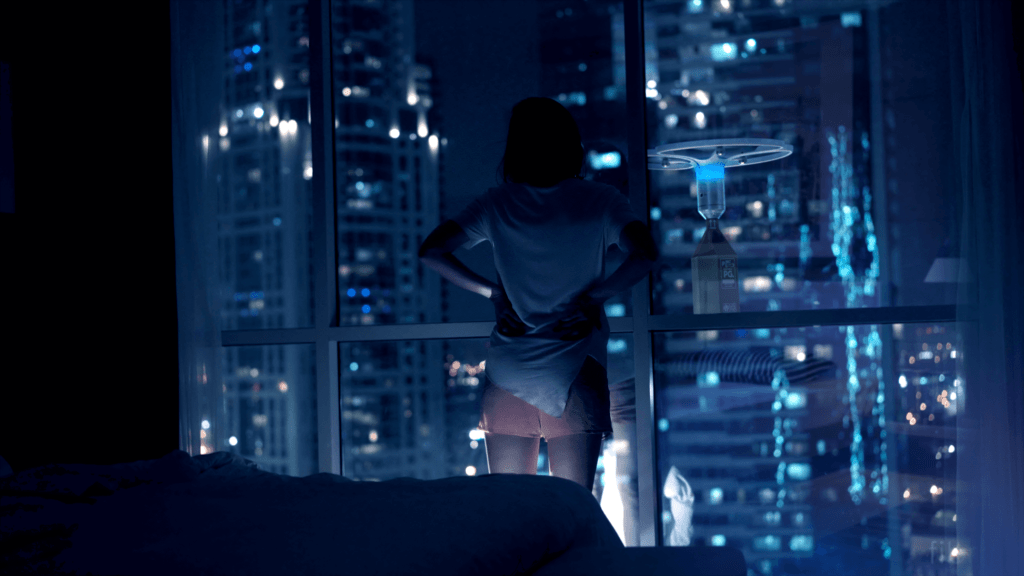 A woman stands inside her skyscraper apartment, with large windows. Other skyscrapers can be seen through her window. A drone carrying a package is hovering outside her window