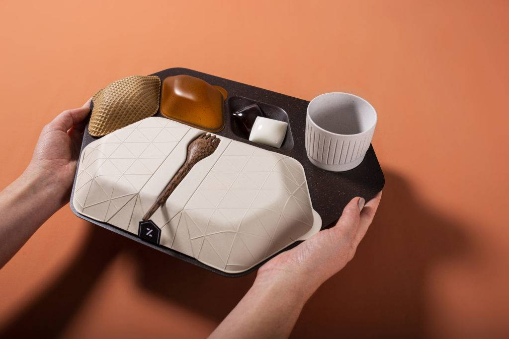 Two hands holding an airline meal tray made from sustainable materials including wafer biscuit, algae, coconut wood and ground coffee
