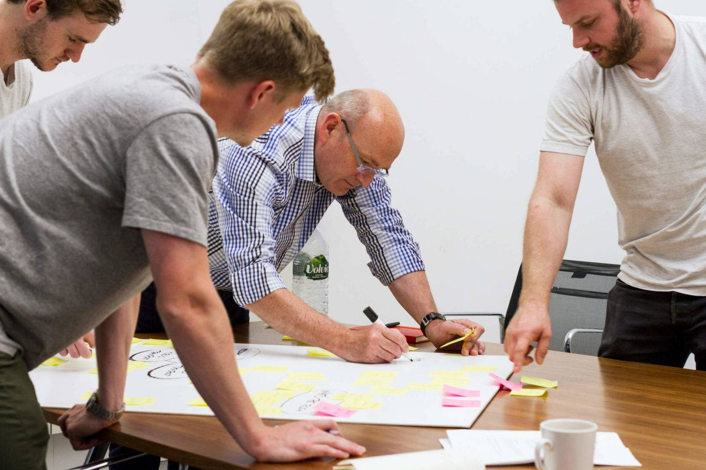Four people leaning over a table, one of them drawing on a large sheet of paper