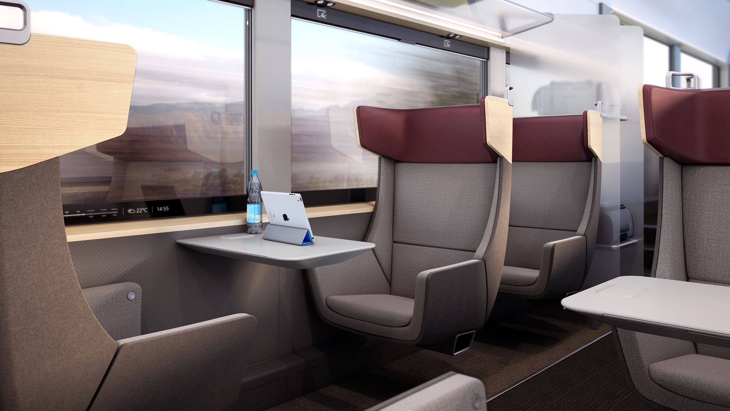 A first class train carriage. A small table features between two seats facnig one another. A tablet and water bottle are placed on the table. Large windows feature on the side