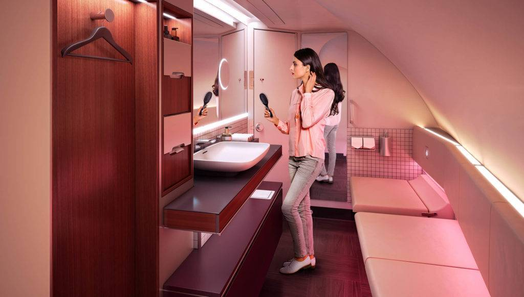 A woman stands in front of a large mirror in the luxurious Premium bathroom on Qatar Airways A380