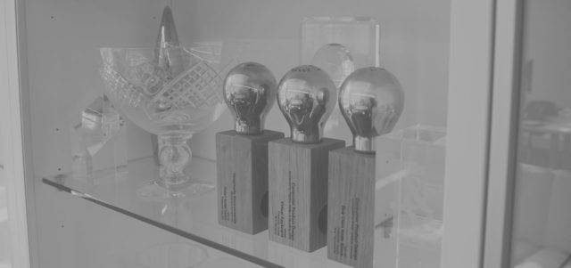 Awards on a glass shelf in a cabinet