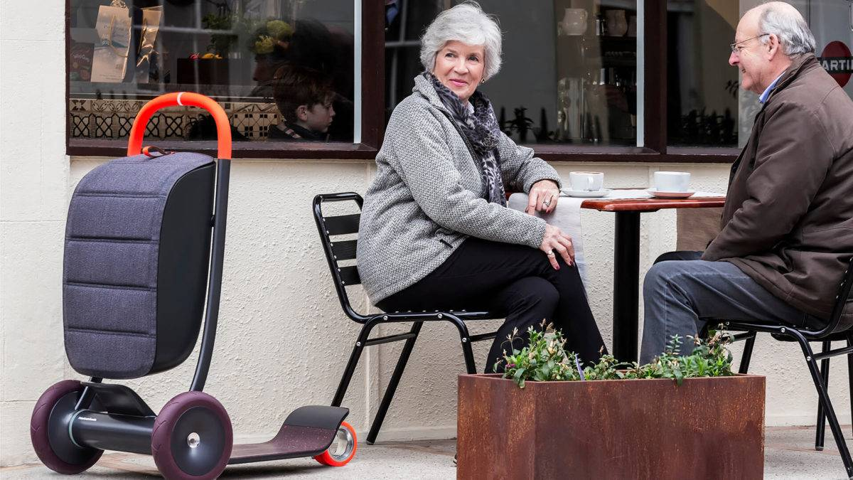 An older couple sit at an outdoor table in a cafe, with a three-wheeled personal scooter next to the woman