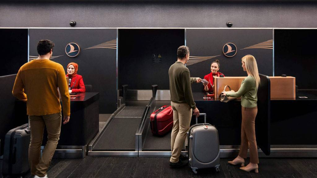 Passengers talking to staff at Turkish Airlines business class check in at New Istanbul Airport