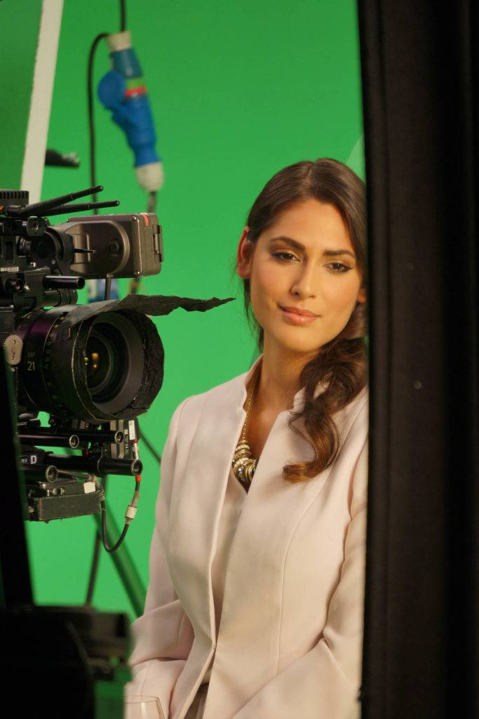 Woman at a film shoot in front of a camera with a green screen background