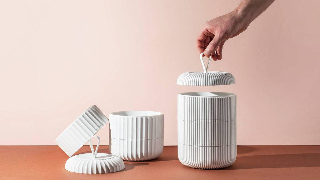 A hand lifting the lid of a white 3D printed model of the bento box style stacked food containers. A second, partly unstacked model sits on the left. The products are laid out on a terracotta surface against a light pink background